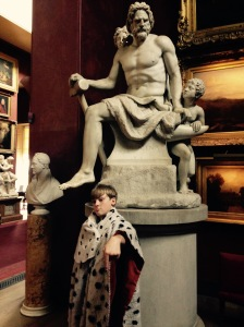 King George posing  with a bear chested statue.